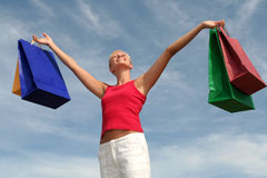 Happy woman with shopping bags. Young woman with arms outstretched holding shopping bags stock photography