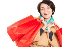 Happy woman with shopping bags in beige autumn coat Royalty Free Stock Photos