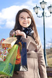 Happy woman with shopping bags and blue sky Stock Photo