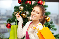 Happy woman with shopping bags and christmas tree Stock Photos