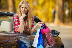 Happy woman with shopping bags in convertible car Royalty Free Stock Photo