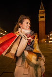 Happy woman with shopping bags looking on something. Venice Stock Photos