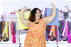 Happy woman with shopping bags at the mall. Image of fat woman looks happy while carrying shopping bags and standing in the mall Royalty Free Stock Photo