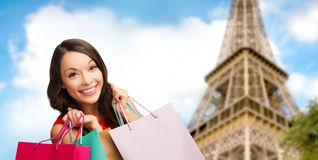 Happy woman with shopping bags over eiffel tower Stock Images