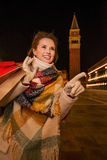 Happy woman with shopping bags pointing on something. Venice Stock Image