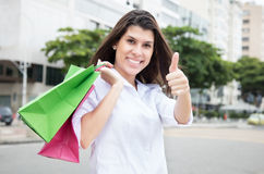 Happy woman with shopping bags showing thumb in city Royalty Free Stock Photo