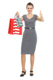 Happy woman with shopping bags showing thumbs up Royalty Free Stock Photography