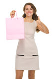 Happy woman with shopping bags showing thumbs up Royalty Free Stock Image