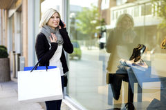 Happy Woman With Shopping Bags Using Mobile Phone Outside Boutiq Royalty Free Stock Photos