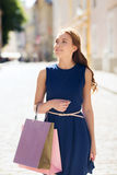 Happy woman with shopping bags walking in city Royalty Free Stock Photos