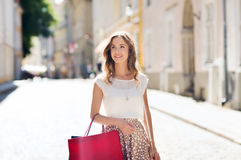 Happy woman with shopping bags walking in city. Sale, consumerism and people concept - happy young woman with shopping bags walking along city street royalty free stock photography