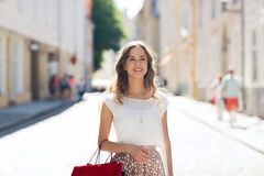 Happy woman with shopping bags walking in city Stock Photos