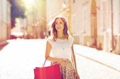 Happy woman with shopping bags walking in city Royalty Free Stock Photography