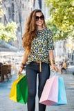 Happy woman with shopping bags walking near Sagrada Familia Stock Photos