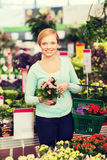 Happy woman with shopping basket choosing flowers Stock Photo