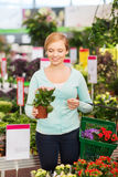 Happy woman with shopping basket choosing flowers Royalty Free Stock Images