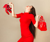 Happy woman after shopping. Beautiful woman in little red dress holding high heel shoes and handbag Royalty Free Stock Photos