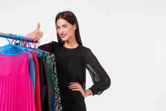 Happy woman shopping and choosing clothes isolated on a white background. Beautiful brunette chooses dress Royalty Free Stock Photos