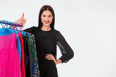 Happy woman shopping and choosing clothes isolated on a white background. Beautiful brunette chooses dress Stock Photos