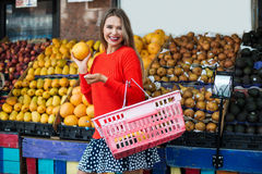 Happy Woman shopping in grocery store and selecting fruits. Stock Photos