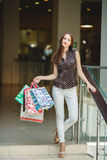 Happy woman shopping and holding bags at the mall Stock Image