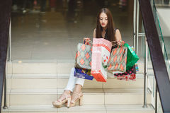 Happy woman shopping and holding bags at the mall Royalty Free Stock Photos