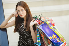 Happy woman shopping and holding bags at the mall Stock Images