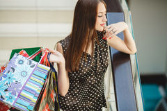 Happy woman shopping and holding bags at the mall Stock Photos