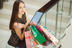 Happy woman shopping and holding bags at the mall Stock Photography