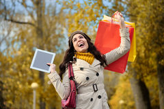 Happy woman shopping and holding digital tablet Stock Image
