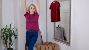 Happy woman after shopping at home try on new clothes. Cute blonde look at mirror and enjoy her wardrobe stock video