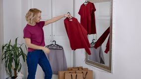 Happy woman after shopping at home try on new clothes. Cute blonde look at mirror and enjoy her wardrobe stock video footage