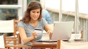Woman shopping online in a coffee shop. Happy woman shopping with a laptop and paying with credit card in a coffee shop stock video footage