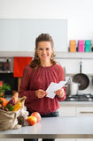 Happy woman with shopping list and bag of fresh produce. An elegant woman is looking up from her shopping lists, smiling happily. On the kitchen counter, a Royalty Free Stock Photo