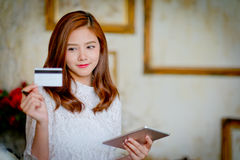 Happy woman shopping online, holding credit card, using tablet c Royalty Free Stock Photo
