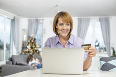 Happy woman shopping online at home during Christmas Royalty Free Stock Photos