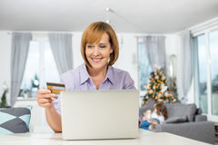 Happy woman shopping online at home during Christmas royalty free stock image