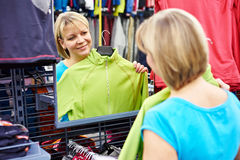 Happy woman shopping for sportswear in shop Stock Images