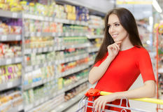 Happy Woman Shopping  at The Supermarket. Portrait of a young girl in a market store with a shopping cart Stock Image