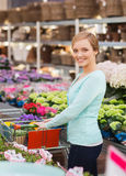 Happy woman with shopping trollye buying flowers Stock Photography