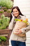 Happy woman shopping vegetables calling cell phone Royalty Free Stock Photo