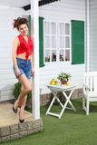Happy woman in shorts poses next country house. And table with fruits Stock Images