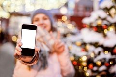 Woman taking selfie in front of the christmas tree. Winter holidays stock images