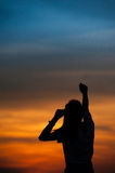 Happy woman show hand up for success. And sunset silhouette royalty free stock images