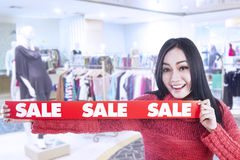 Happy woman show winter sale banner in mall. Woman is holding a red banner of winter sale in shopping mall Royalty Free Stock Image