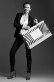 Happy woman showing big shopping bag against grey background Royalty Free Stock Image