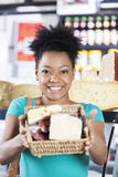 Happy Woman Showing Cheese Basket In Grocery Store Stock Images