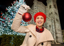 Happy woman showing Christmas ball near Duomo in Florence, Italy. Happy young woman in white coat showing Christmas ball while near Christmas tree and Duomo in royalty free stock photo
