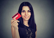 Happy woman showing credit card isolated on gray background stock images