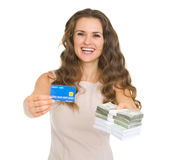 Happy woman showing credit card and money packs Royalty Free Stock Photo
